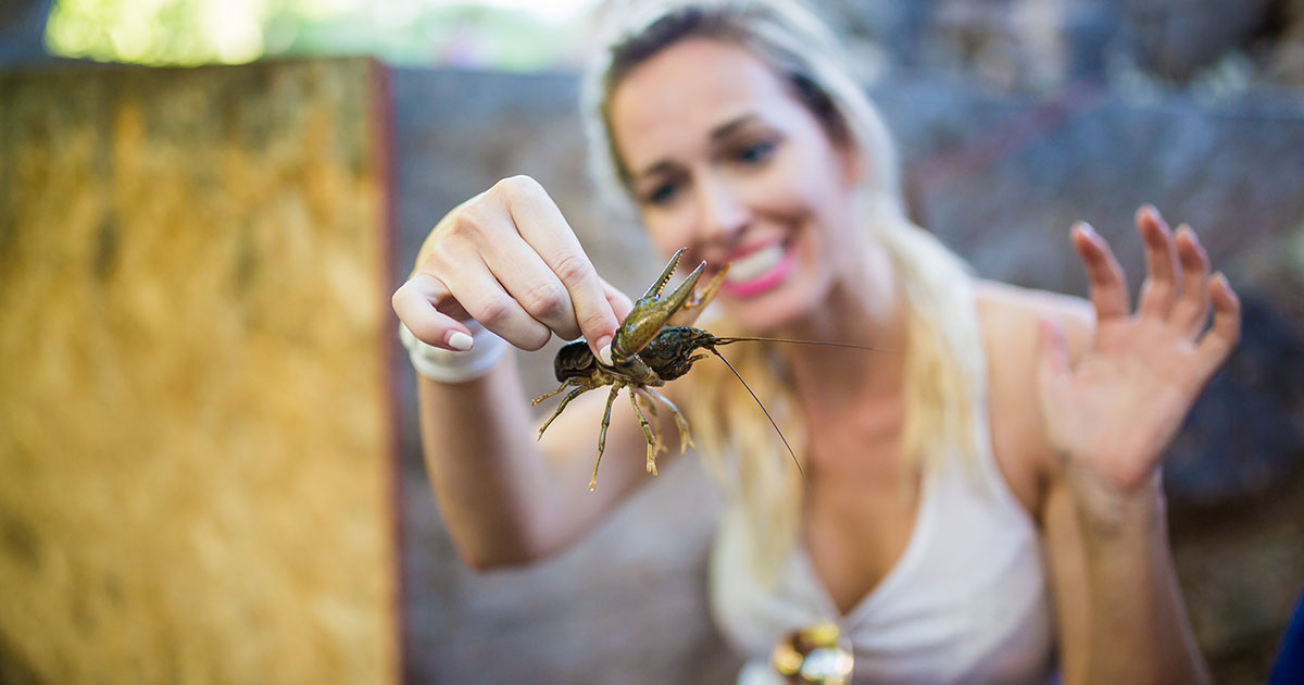 Photograph of a woman holding a crawdad caught inside Crawdad Canyon.